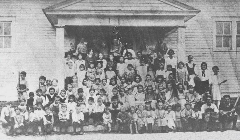 Large class of school children posingin front of the school