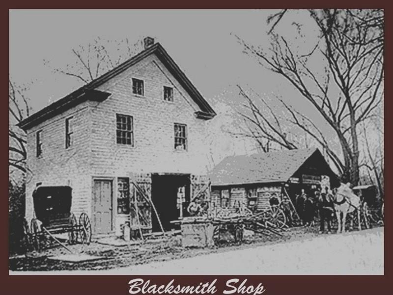Grainy photo of blacksmith shop with carriages