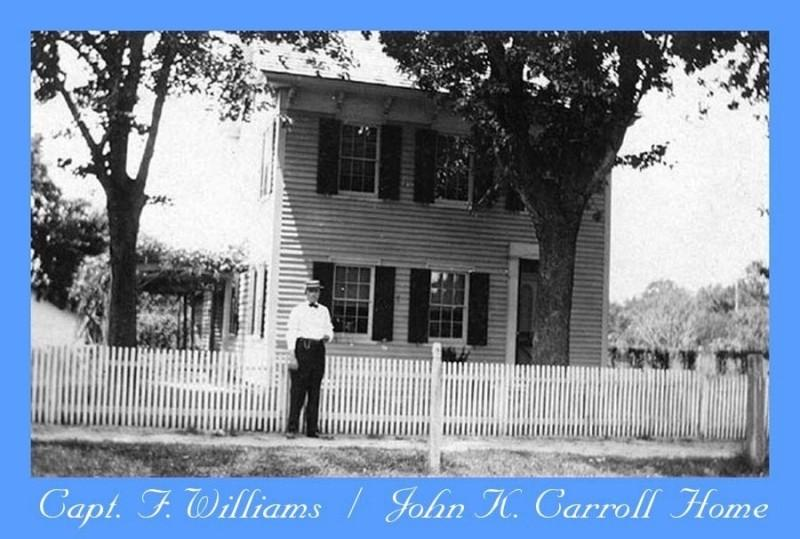 House with white picket fence and man standing in front