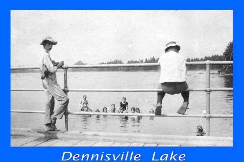 Boys on bridge railing and children in water at Dennisville Lake