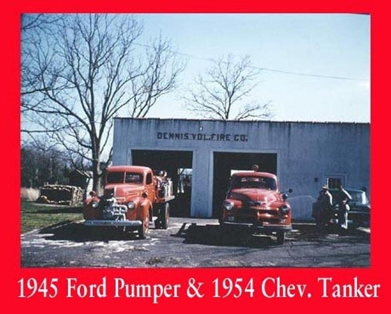 Old trucks parked in front of the Dennis Fire station