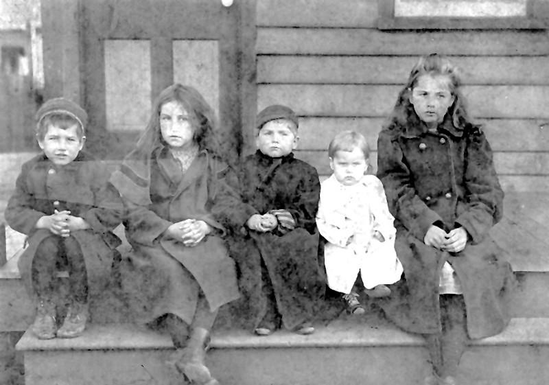 Five children of Cole family sitting on stoop
