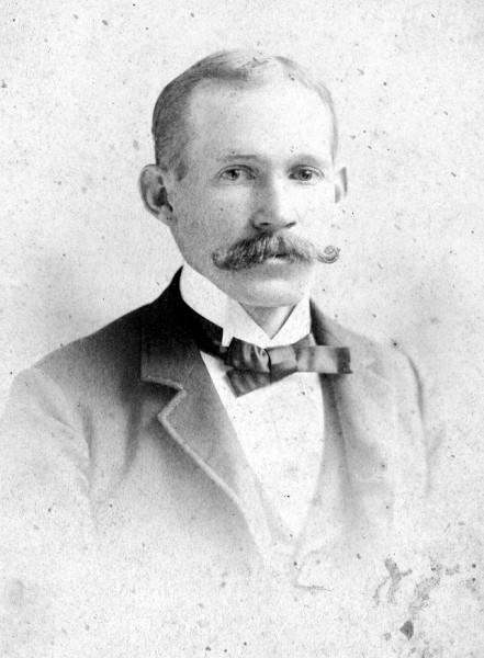 Man with moustache named John King Carroll