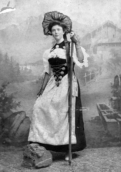 Woman named Mary Ruchle wearing a fancy dress and carrying a walking stick