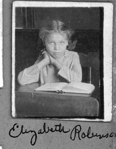 Young girl sitting at school desk with open book identified as Elizabeth Robinson