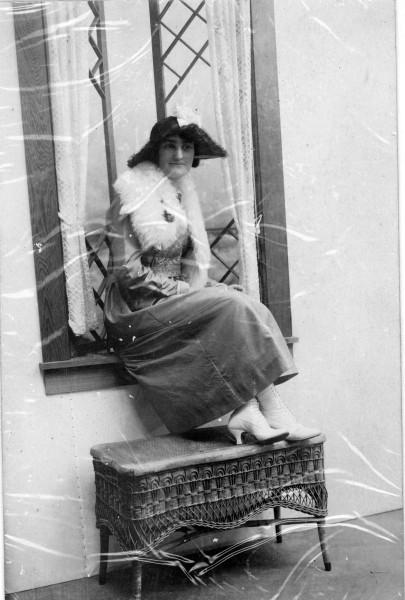 Lady named Mae Scull posing while sitting on windowsill and feet on a bench