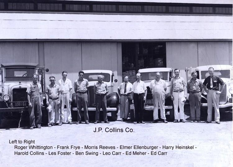 Men working at JP Collins standing in front of vintage vehicles
