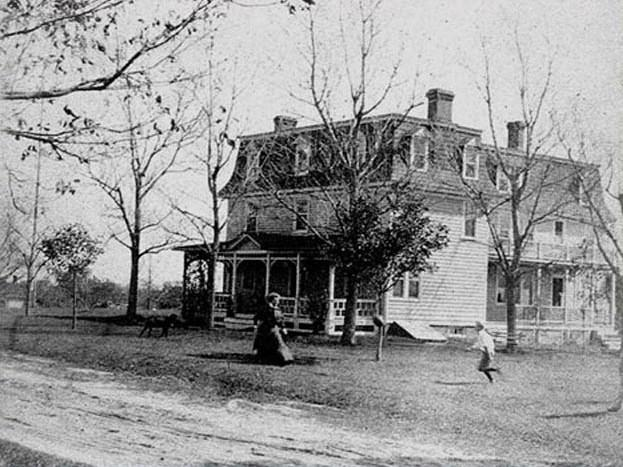 Van Guilders house with woman and child playing outside
