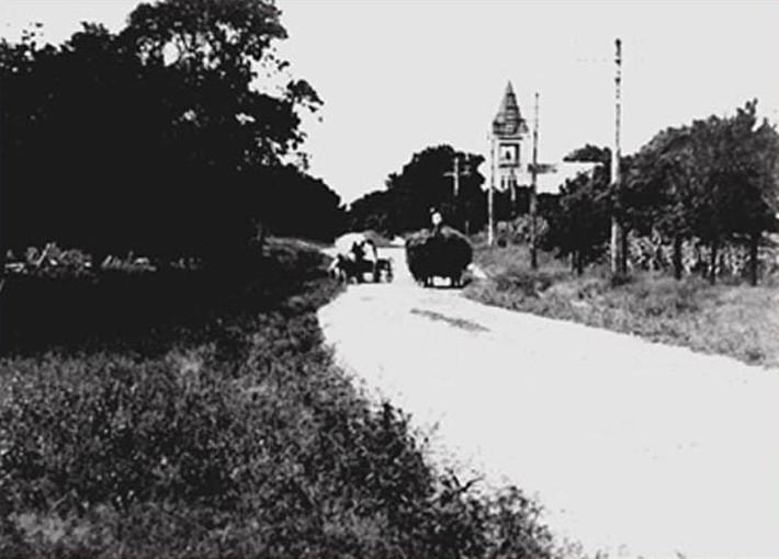 Hay wagon on road with church in distance