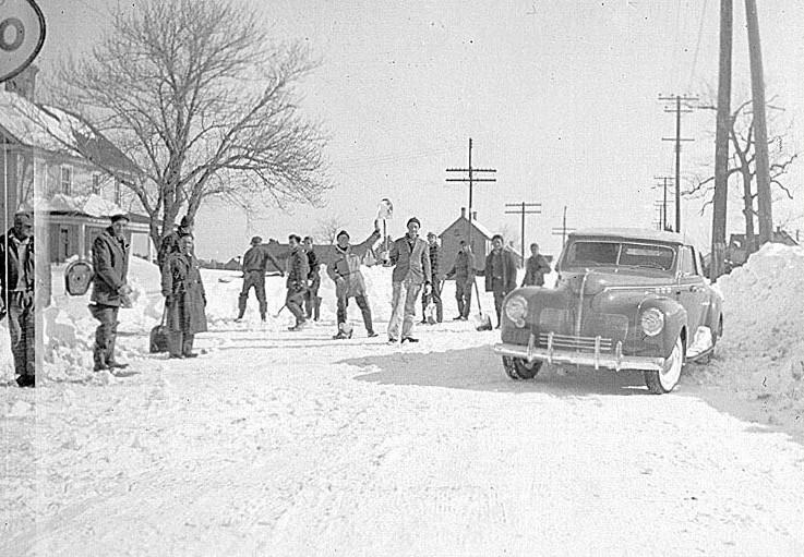 Men clearing snow with car parked by a snow pile