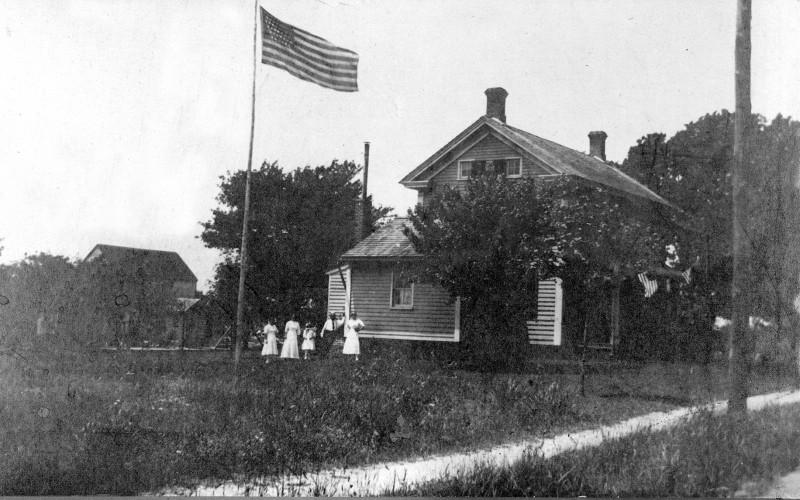 Abrams – Bushey House with American Flag flying in foreground