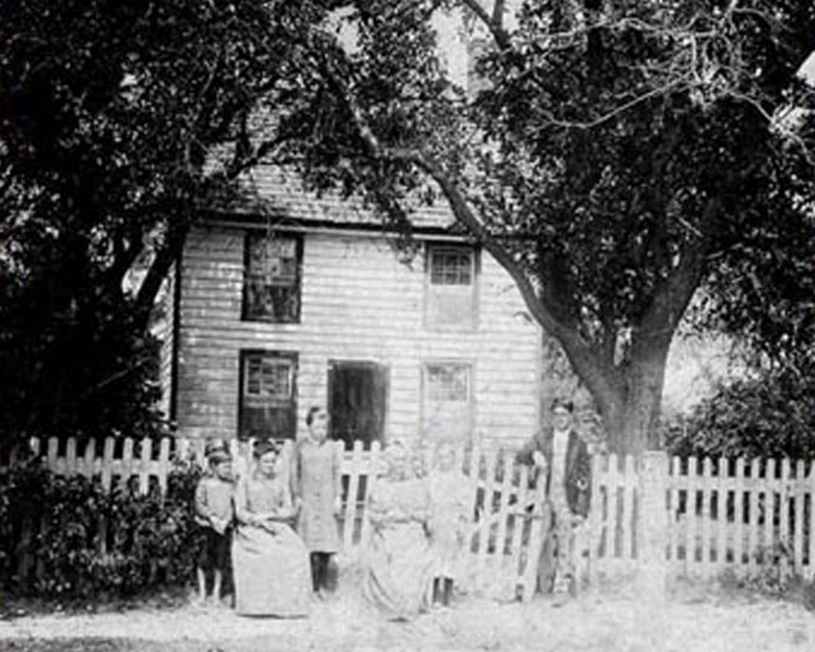 Nickerson home with family posing in front of it
