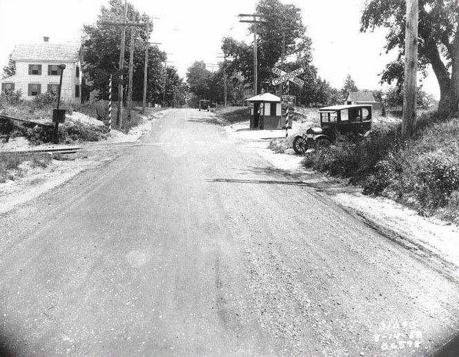 Unpaved road with a Railroad crossing signal and an antique car