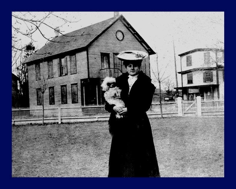 Well dressed lady olding a small fluffy dog and standing in front of Alpha Hall