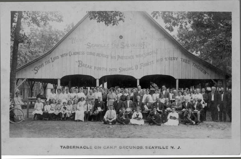 Tabernacle of the bible camp with large group of people in front