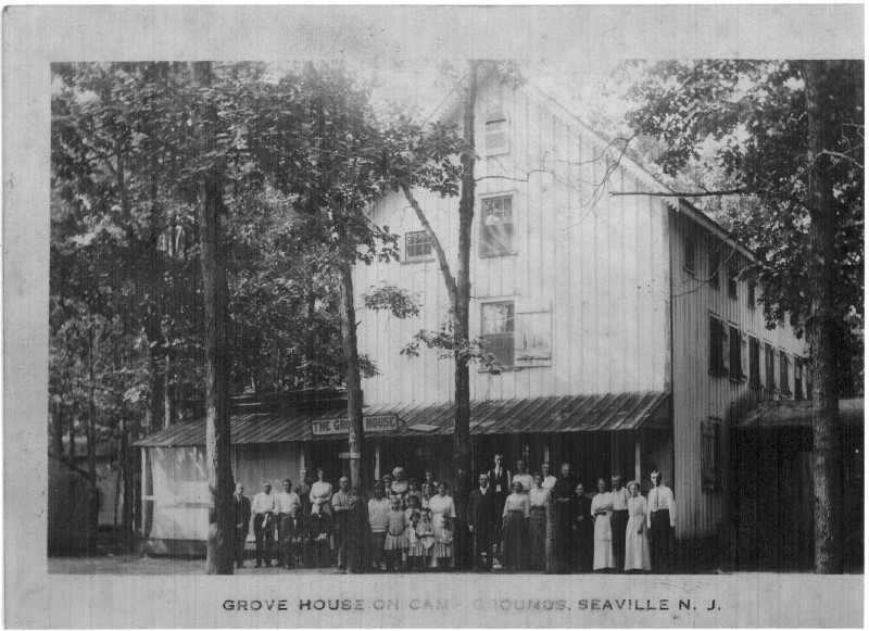 Old Grove House with grop of people in front posing for camera