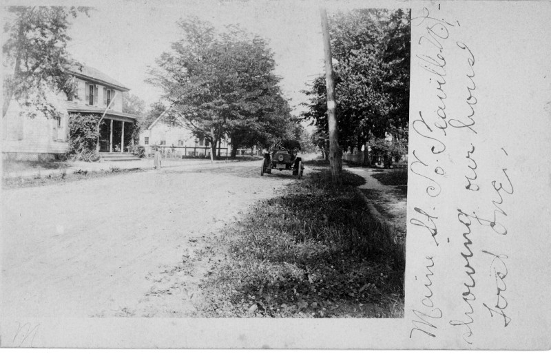Old postcard showing street with old auto