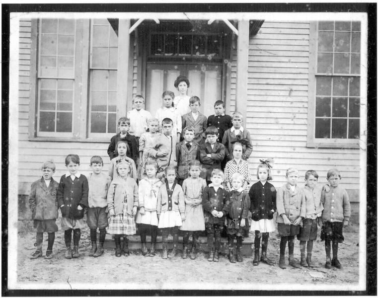 School childen and teacher in front of school