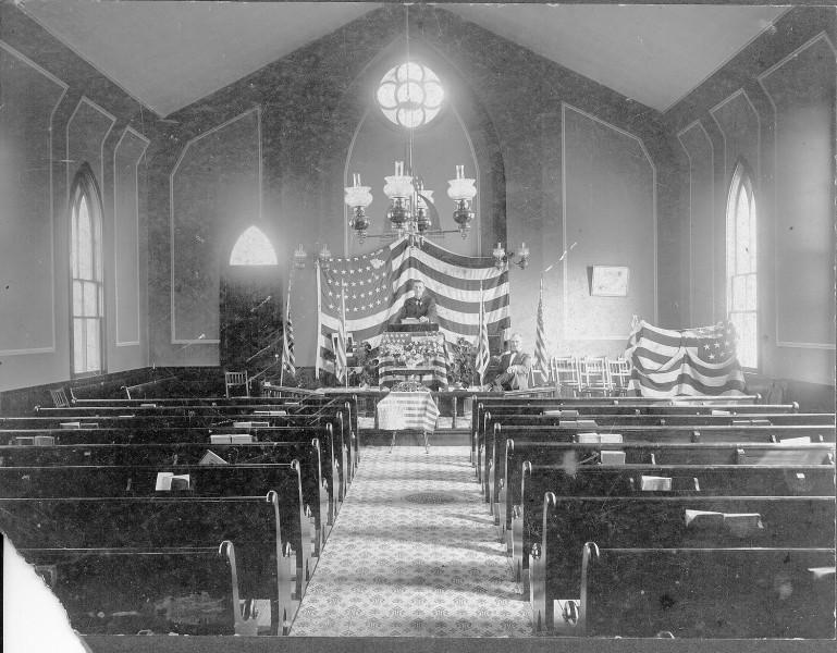 Interior of Methodist church with flag draped behind podium
