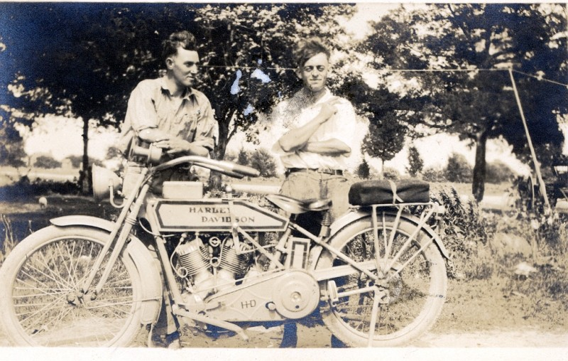 Two men posing with antique Harley Davidson motorcycle