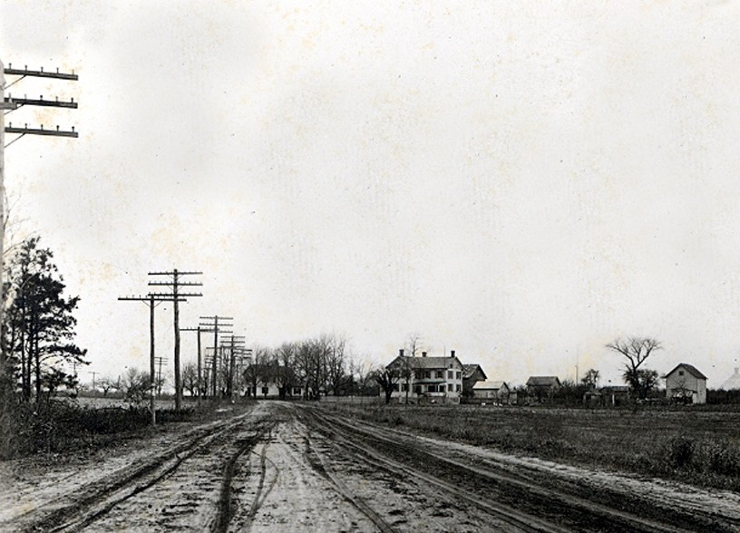 Railroad tracks with buildings in back and electric poles