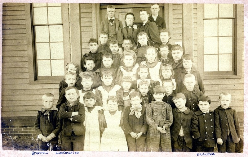 School children of different ages posing in front of school