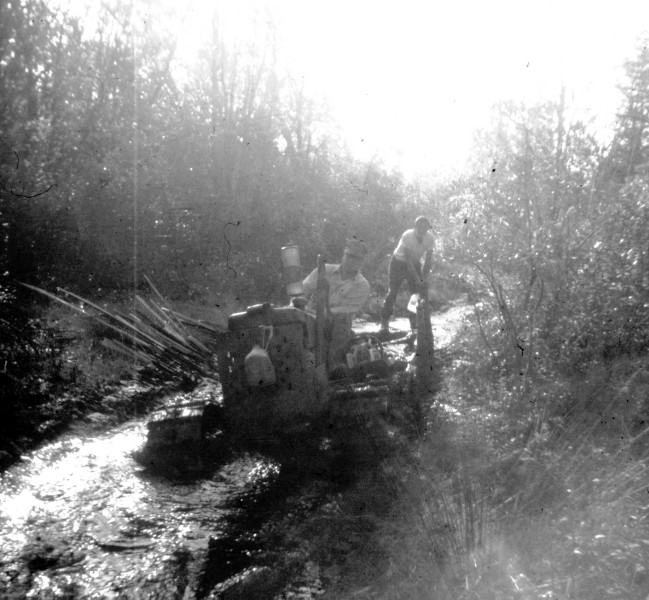 Old John Deere tractor driving along a creek