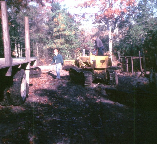Small grader helping load logs onto a truck