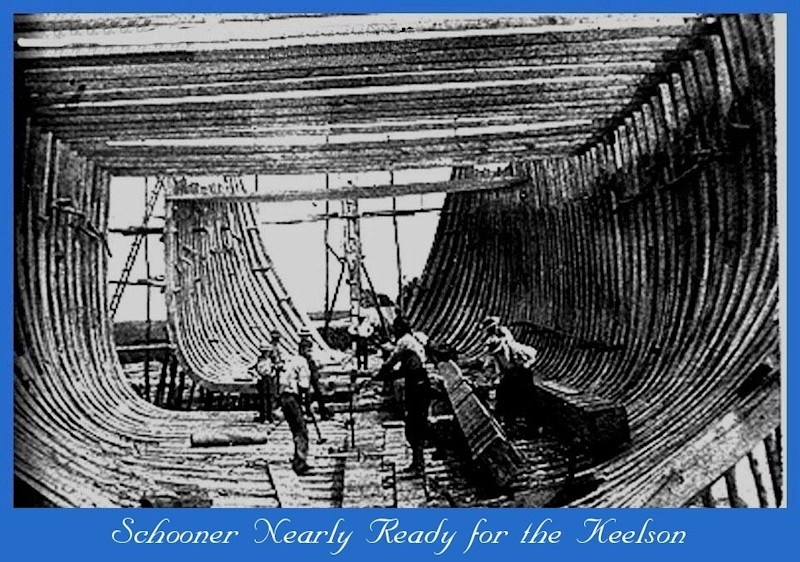 Workers inside the framing of a schooner under construction