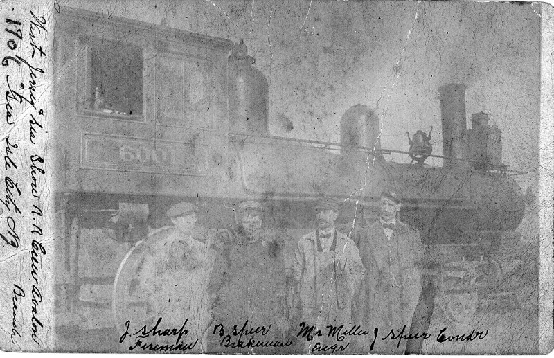 Old faded photo of crew standing in front of Engine 6001
