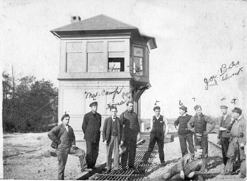 Workers standing around South Seaville train control tower